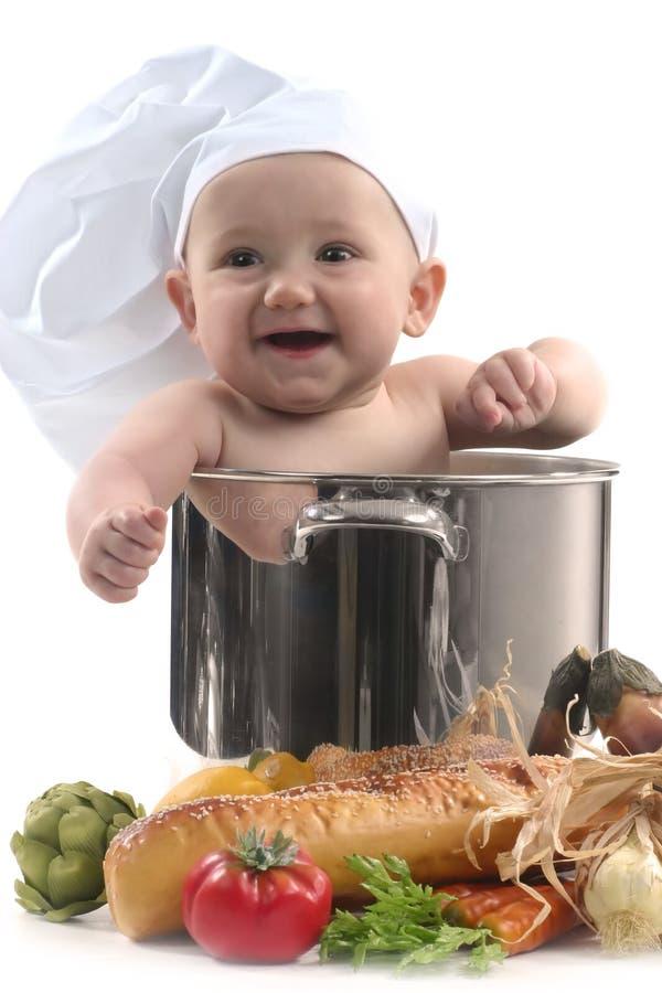 Bambino sveglio in un sorridere del POT del cuoco unico fotografia stock