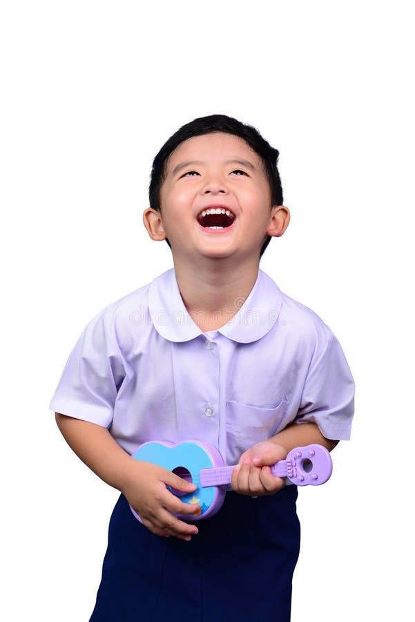Bambino tailandese asiatico dello studente di asilo in uniforme scolastico che gioca la chitarra del giocattolo isolata su fondo  fotografia stock libera da diritti