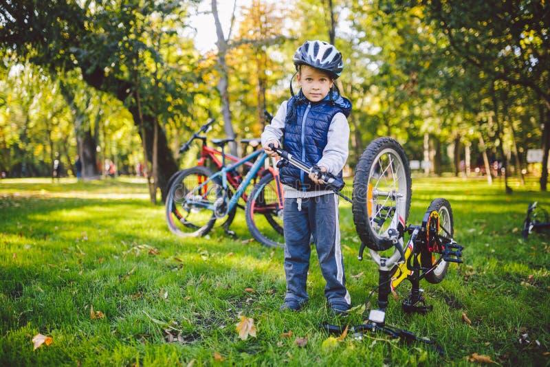 Bambino tematico e professione Un piccolo ragazzo caucasico biondo utilizza una pompa di bicicletta, pompa l'aria in una biciclet fotografia stock libera da diritti
