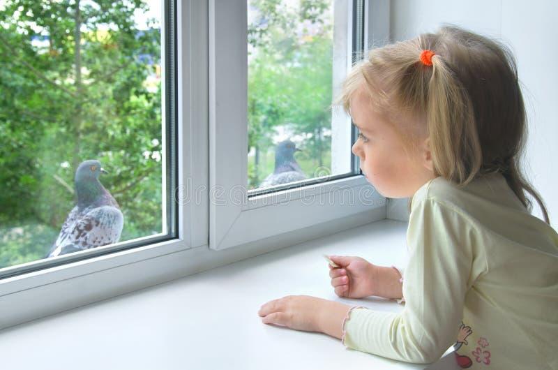 Bambino triste alla finestra fotografia stock