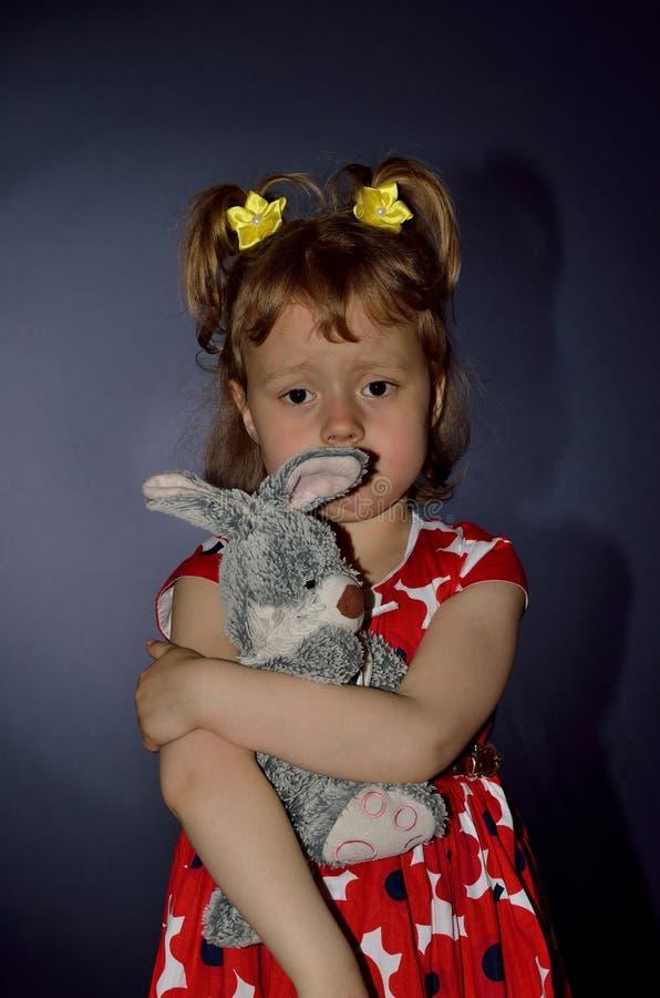 Bambino triste con la fine del giocattolo della peluche su su un fondo blu immagini stock