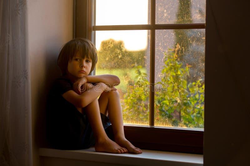 Bambino triste, ragazzo, sedentesi su uno schermo della finestra fotografie stock libere da diritti