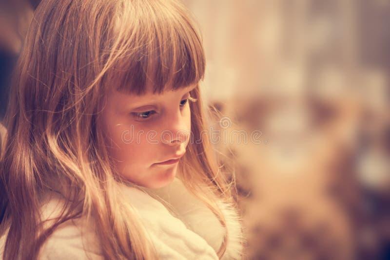 Bambino triste solo con lo sguardo di ribaltamento fotografia stock libera da diritti