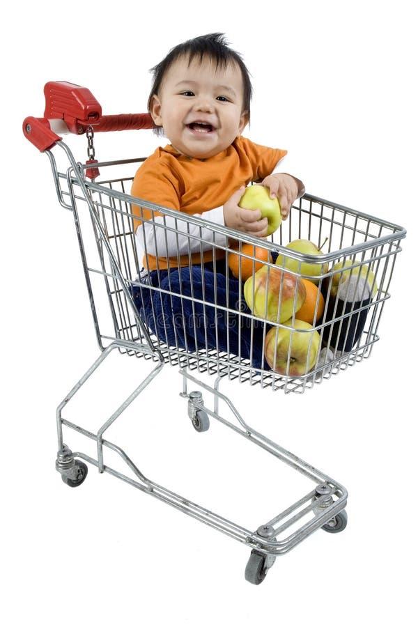 Bambino in un carrello di acquisto fotografia stock