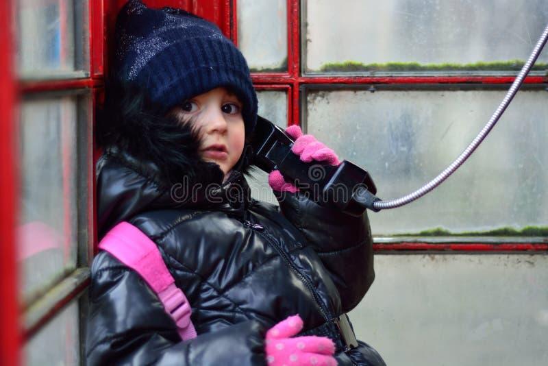 Bambino in una cabina telefonica rossa, sul telefono fotografie stock libere da diritti