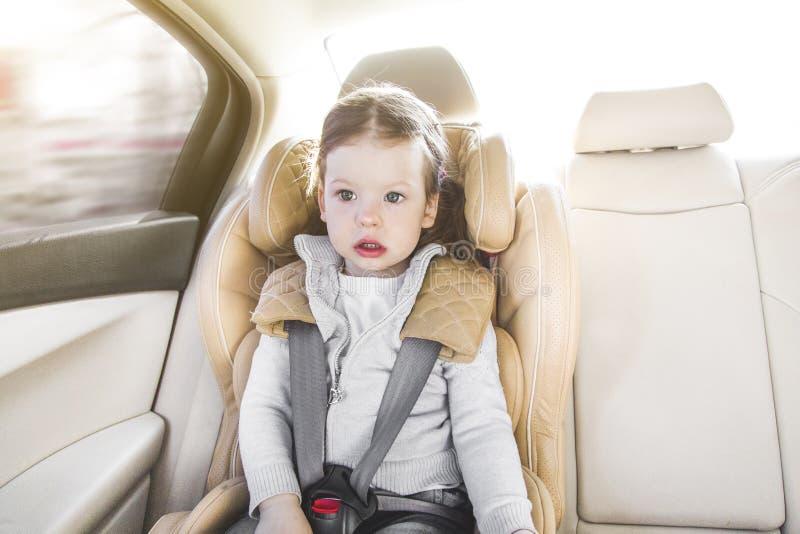 Bambino in una sede di automobile del bambino Pressione di Isofix sede di automobile beige in un salone luminoso Protezione nell' fotografie stock