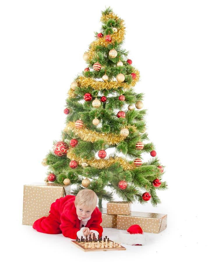 Bambino vestito come gnomo vicino ad un albero di Natale immagine stock