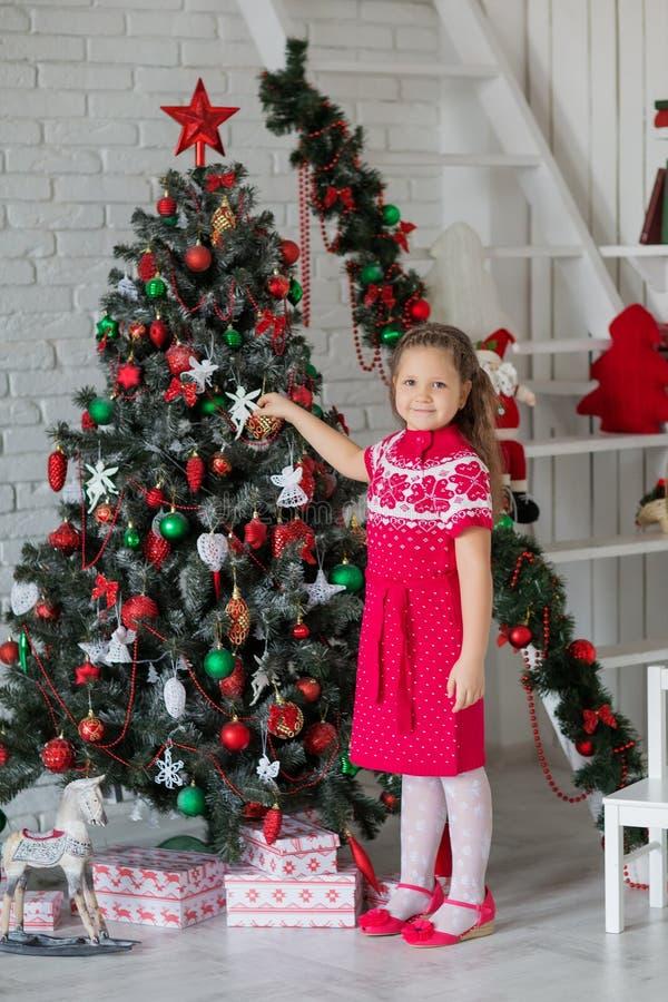 Bambino vicino all'albero del nuovo anno immagine stock libera da diritti