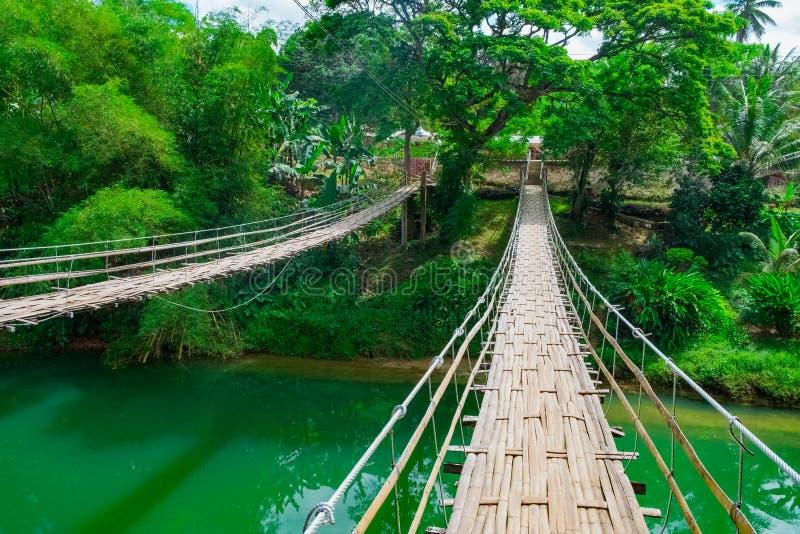 Bamboe hangende brug over rivier stock foto's