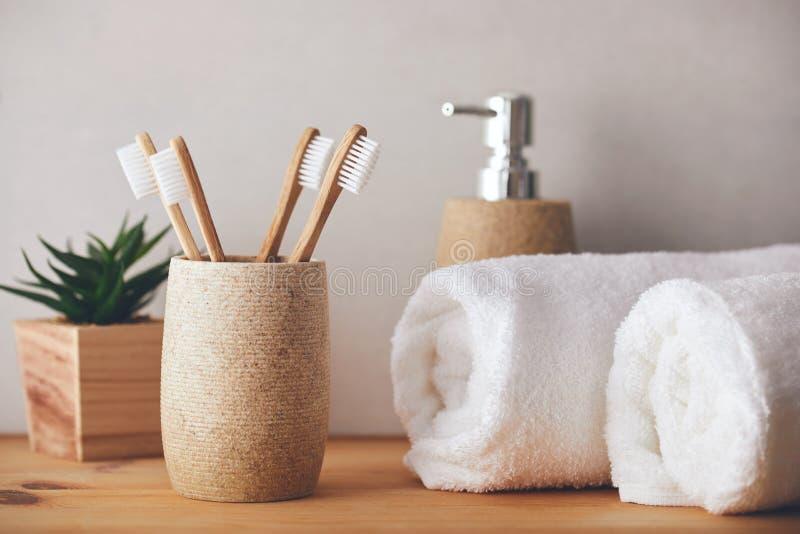 Bamboe tandenborstels in een beker en witte handdoeken stock afbeelding