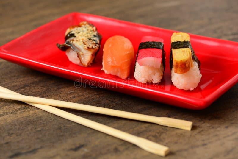 Bamboeeetstokjes en plaat met sushi stock foto's