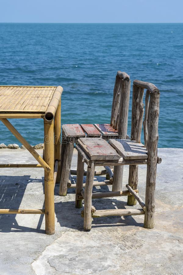 Bamboelijst en houten stoelen in lege koffie naast zeewater in tropisch strand Eiland Koh Phangan, Thailand stock fotografie