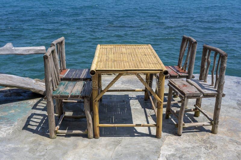 Bamboelijst en houten stoelen in lege koffie naast zeewater in tropisch strand Eiland Koh Phangan, Thailand stock afbeelding