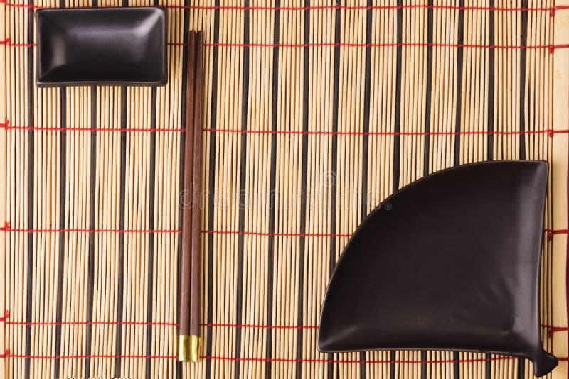 Bamboemat met twee sushieetstokjes en koppen voor sojasaus Achtergrond voor menu royalty-vrije stock afbeelding