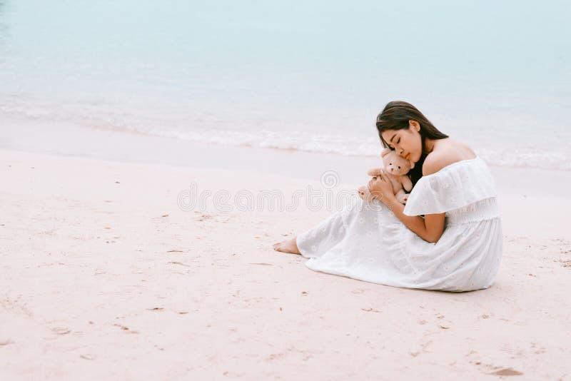 Bambola asiatica dell'orso dell'abbraccio della donna ed amore aspettante che fanno il suo hap fotografia stock