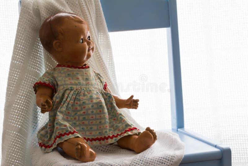 Bambola ceramica d'annata con una coperta bianca che si siede su una sedia blu della scuola materna fotografia stock libera da diritti