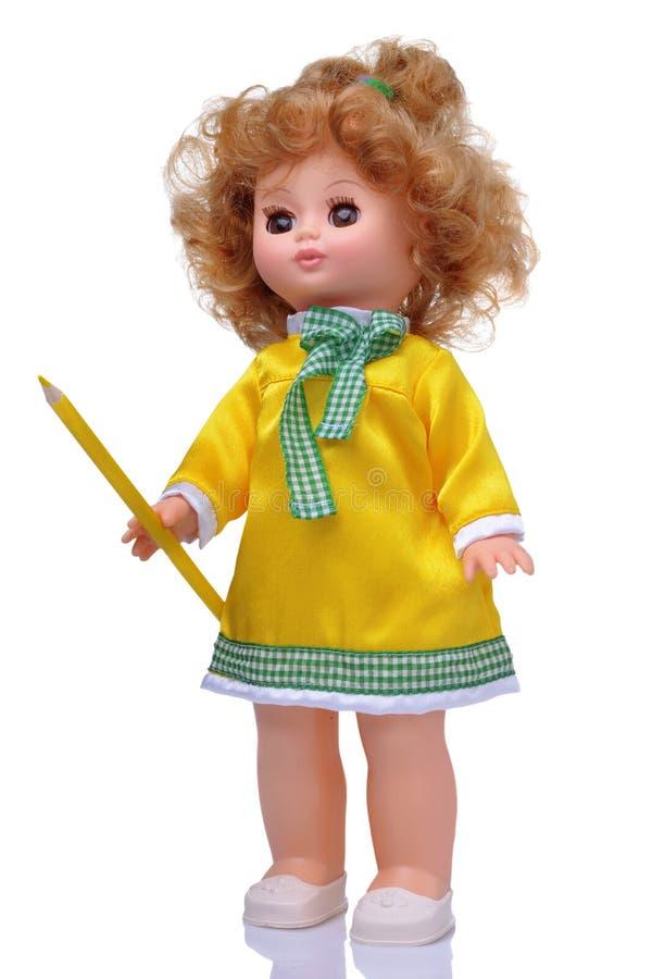 Bambola d'annata in vestito giallo con la matita fotografia stock libera da diritti