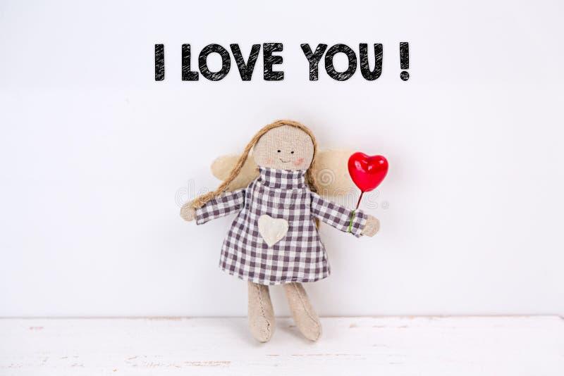 """Bambola del burattino con un cuore e un testo rossi """"ti amo """"su un fondo bianco fotografie stock"""