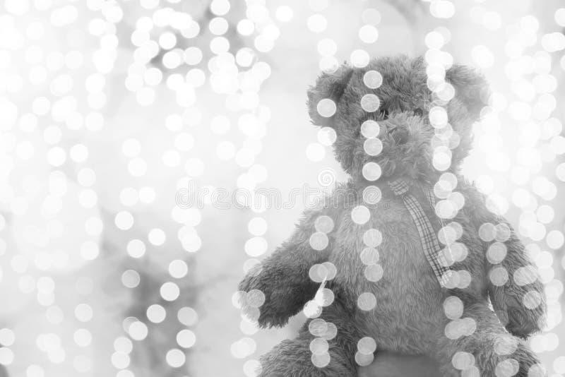 Bambola dell'orsacchiotto nella linea di illuminazione argento del bokeh luminoso per il Natale o il fondo del buon anno, seduta  fotografie stock libere da diritti