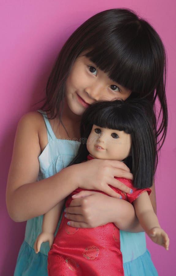 Bambola della holding della ragazza fotografia stock