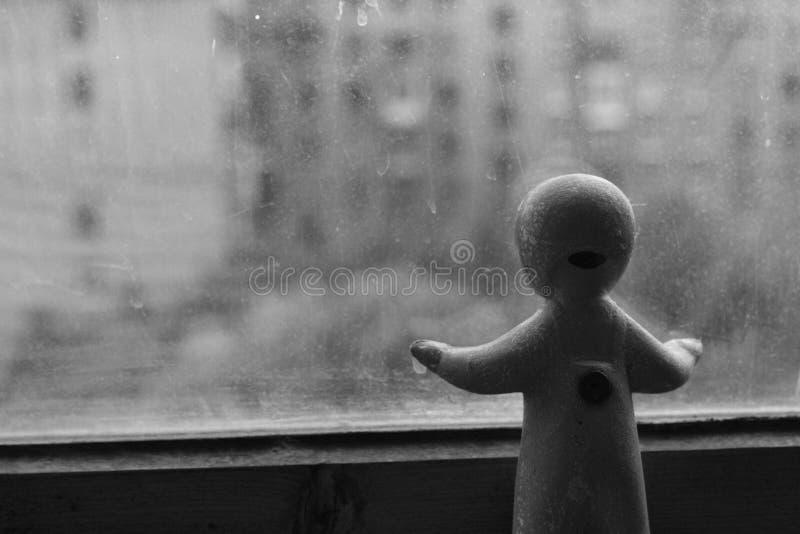 bambola della parte del bambino che osserva fuori finestra fotografie stock