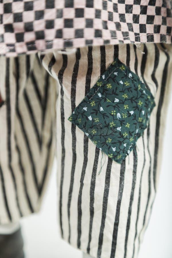 Bambola fatta a mano della porcellana ceramica in pantaloni a strisce con le toppe fotografia stock