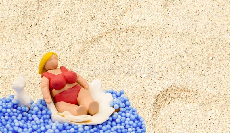 Bambola fatta a mano nella scena della spiaggia Donna turistica con l'ente grasso in bikini rosso fotografia stock