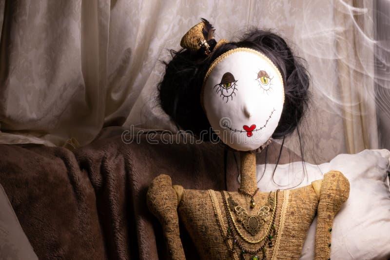 Bambola terrificante nella regolazione misteriosa scura con gli effetti della luce immagine stock