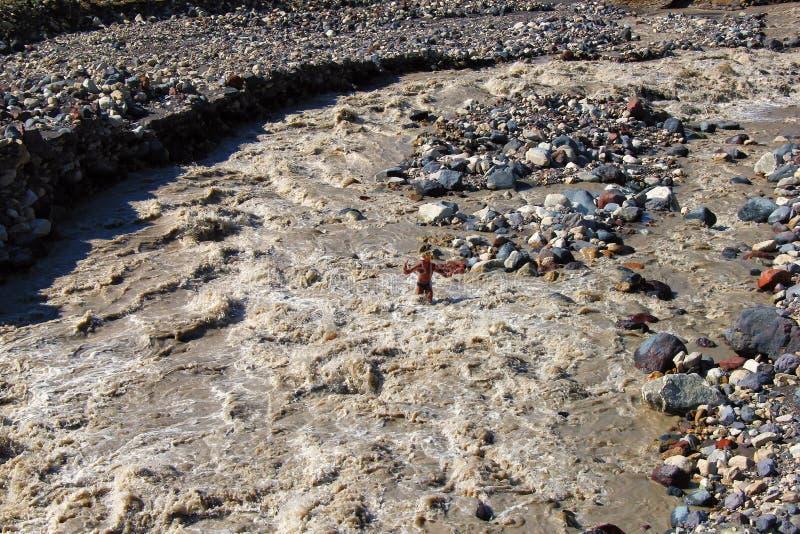 Bamboleo del caminante un río muy áspero de la montaña fotografía de archivo