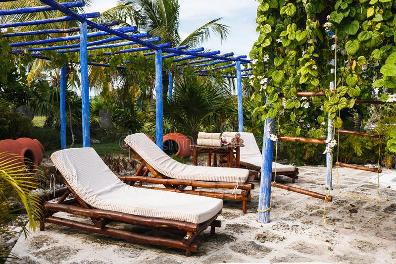 Bamboo bed-chairs, small table are under blue wooden roofless shed in garden. Bamboo bed-chairs and a small table standing under blue wooden roofless shed stock image