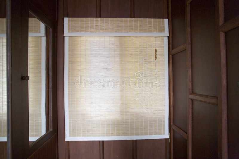 Bamboo Blinds. Bamboo window blinds in a wood paneled room stock photos