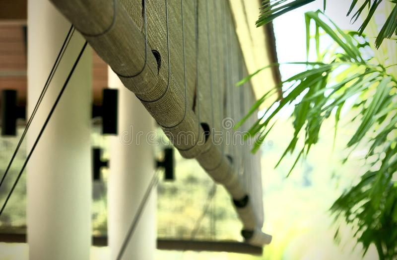 Bamboo blinds asian traditional home decoration. Sunlight coming through bamboo blinds by the window. Bamboo curtain at a window. Overlooking garden stock photo