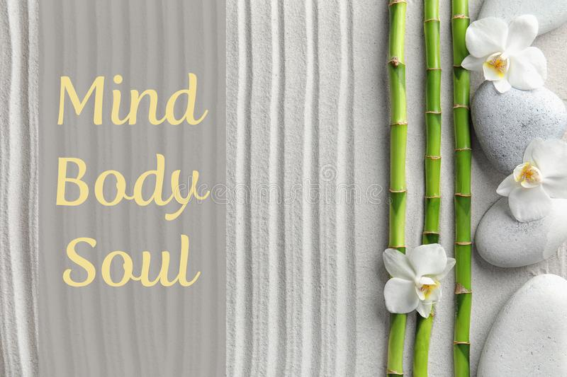 Bamboo branches with spa stones and flowers on sand, top view. stock photography