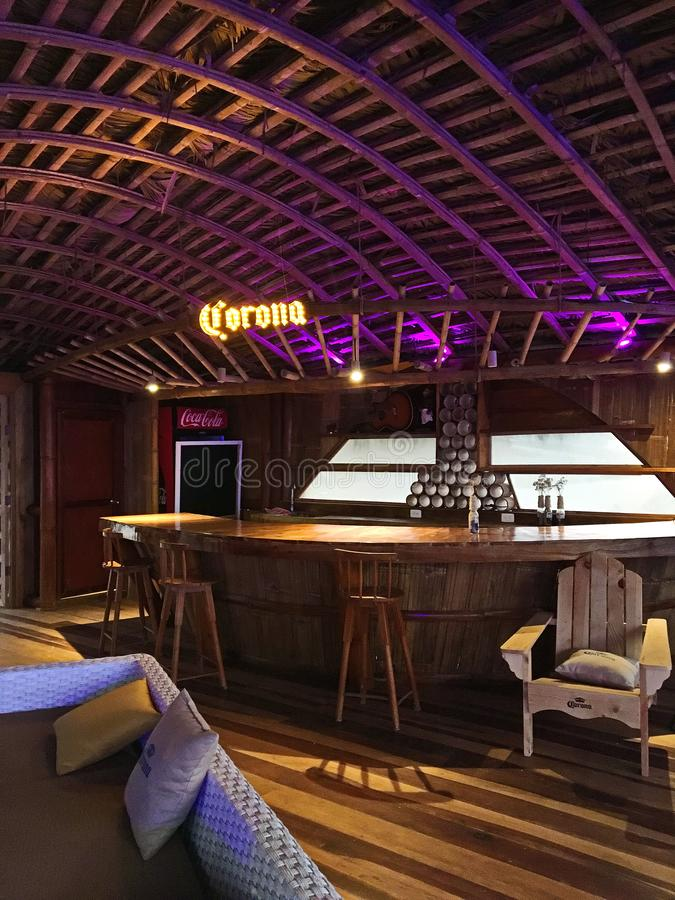 Bamboo Bar Area Overlooking the Ocean. Bamboo built bar with interesting ceiling details, wood bar and stools. Corona and Coca Cola advertising. Rattan woven stock image