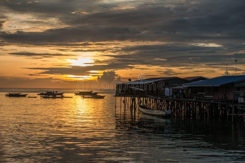 Bamboo bungalows sopra il mare con barche durante l'alba immagini stock libere da diritti