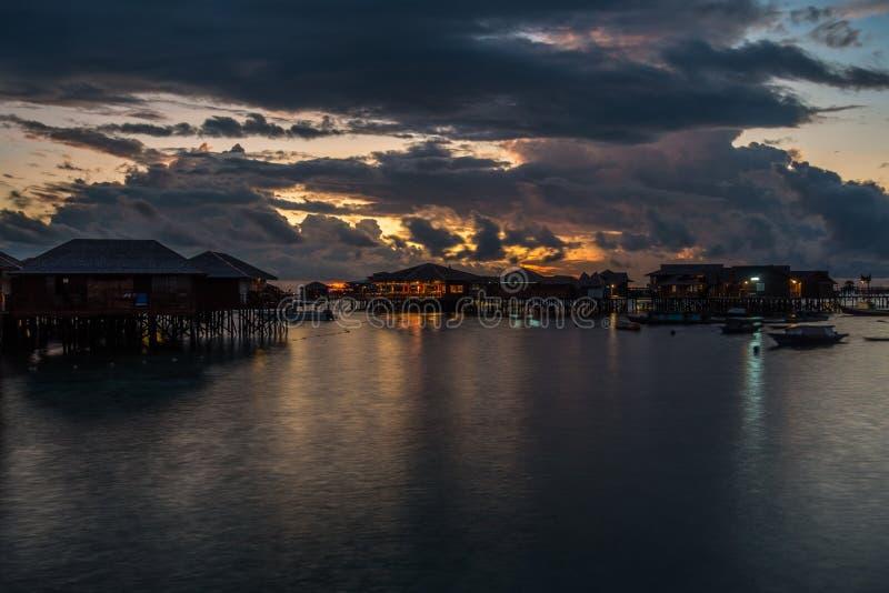 Bamboo bungalows sopra il mare durante l'alba nuvolosa immagini stock