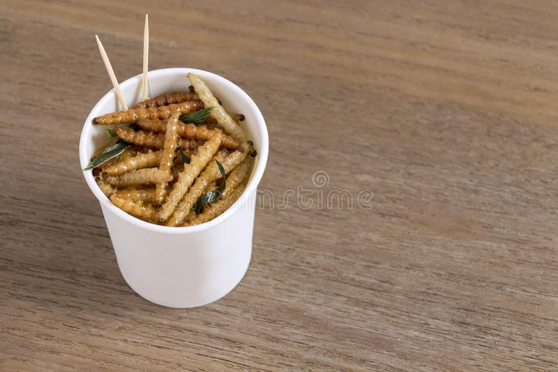 Bamboo Caterpillar insects for eating as food. Worm deep-fried crispy snack in disposable cup for take-away home on wood table royalty free stock photos