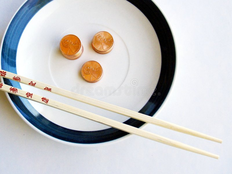 Bamboo chopsticks, plate, and pennies. Bamboo chopsticks on white and green plate containing stacks of bright copper pennies in soft light and shadow against stock photography