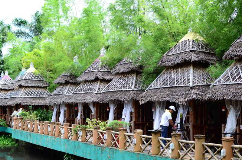 Bamboo and Coconut Leaves Cottage houses line in an Asian aquatic jungle theme park. Calauan Laguna, Philippines - August 28, 2016: Bamboo and Coconut Leaves stock photography
