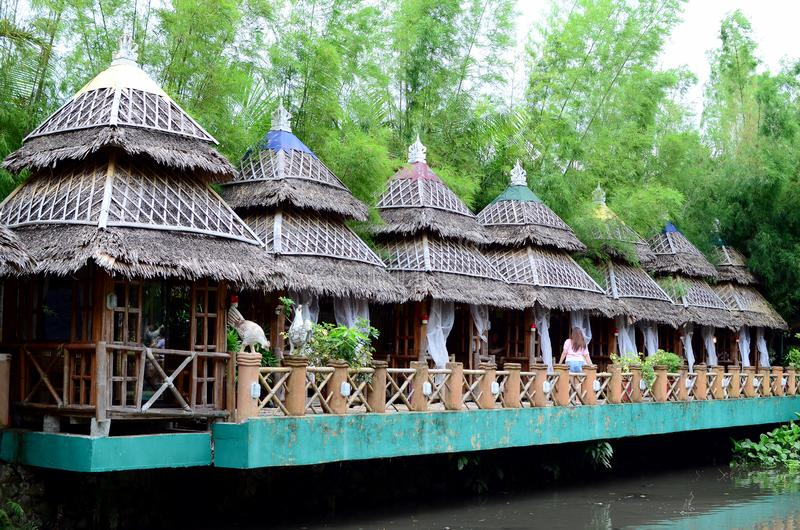 Bamboo and Coconut Leaves Cottage houses line in an Asian aquatic jungle theme park. Calauan Laguna, Philippines - August 28, 2016: Bamboo and Coconut Leaves stock photos