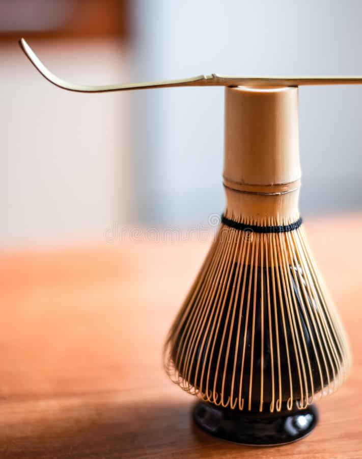 Bamboo corolla on stand and wooden spoon. Tools for whisking Chinese tea matcha royalty free stock photos