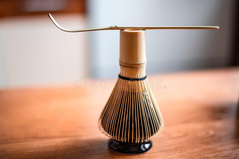 Bamboo corolla on stand and wooden spoon. Tools for whisking Chinese tea matcha stock photos