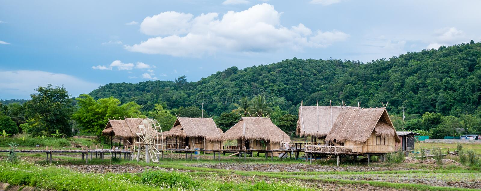 The bamboo cottage, the simple lifestyle of a Thai farmer with a mountainous background below the blue sky at Thailand stock photo