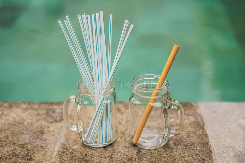 Bamboo drinking straw vs disposable straws on the background of the pool. Zero waste concept.  stock images