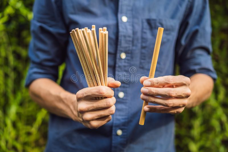 Bamboo drinking straw vs disposable straws in hands. Zero waste concept.  stock images