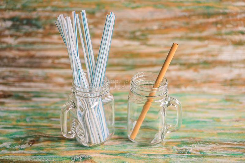 Bamboo drinking straw vs disposable straws on wooden painted background. Zero waste concept.  stock image