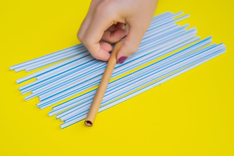 Bamboo drinking straw vs disposable straws on a yellow background. Zero waste concept. Bamboo drinking straw vs disposable straws in on a yellow background. Zero stock photos