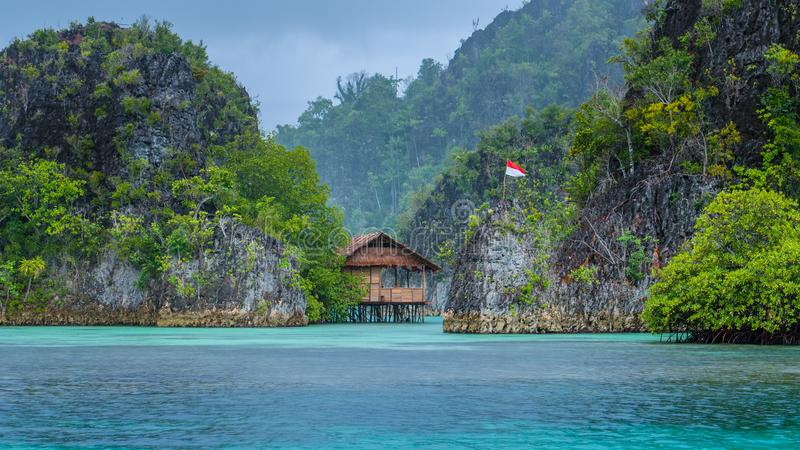 Bamboo Hut between some Rocks under Rain in Bay with Indonesian Flag, Pianemo Islands, Raja Ampat, West Papua, Indonesia royalty free stock photo