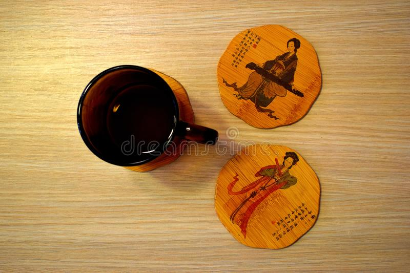 Bamboo illustreted tea cup holder on golden wood background royalty free stock photo