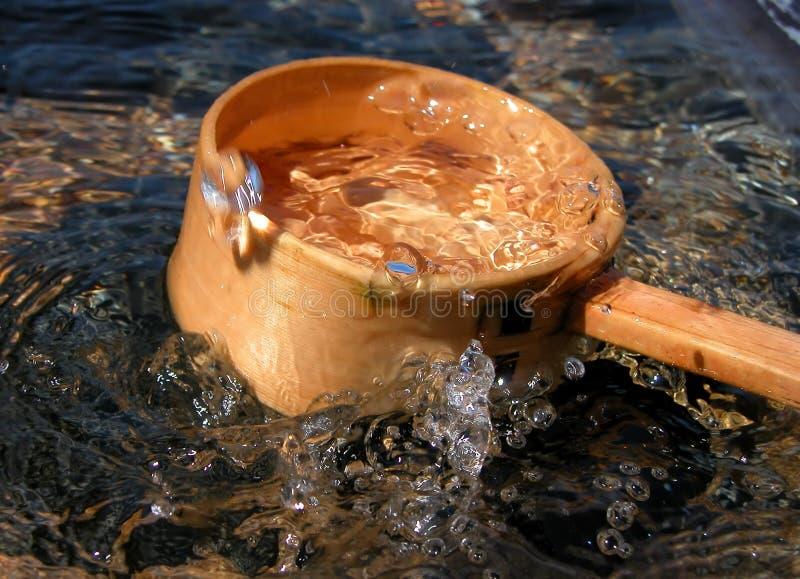 Bamboo ladle and splash royalty free stock photography